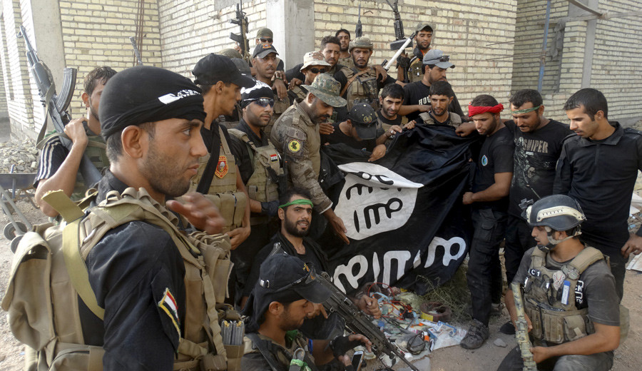 Iraqi security forces hold an Islamist State flag which they pulled down at the University of Anbar, in Anbar province © Stringer
