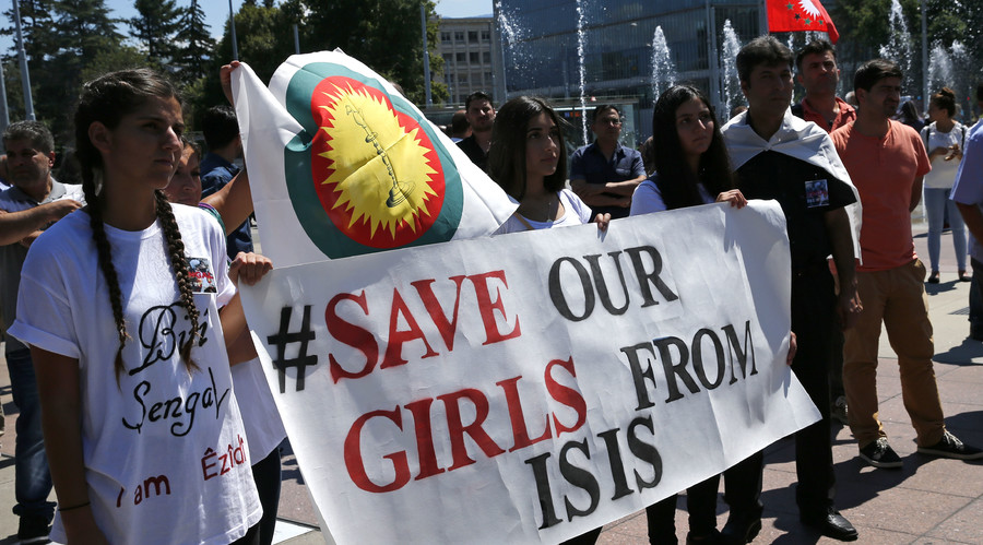 Women hold a banner during a demonstration marking the first anniversary of Islamic State's surge on Yazidis of the town of Sinjar, in front of the United Nations European headquarters in Geneva, Switzerland, August 3, 2015. © Denis Balibouse