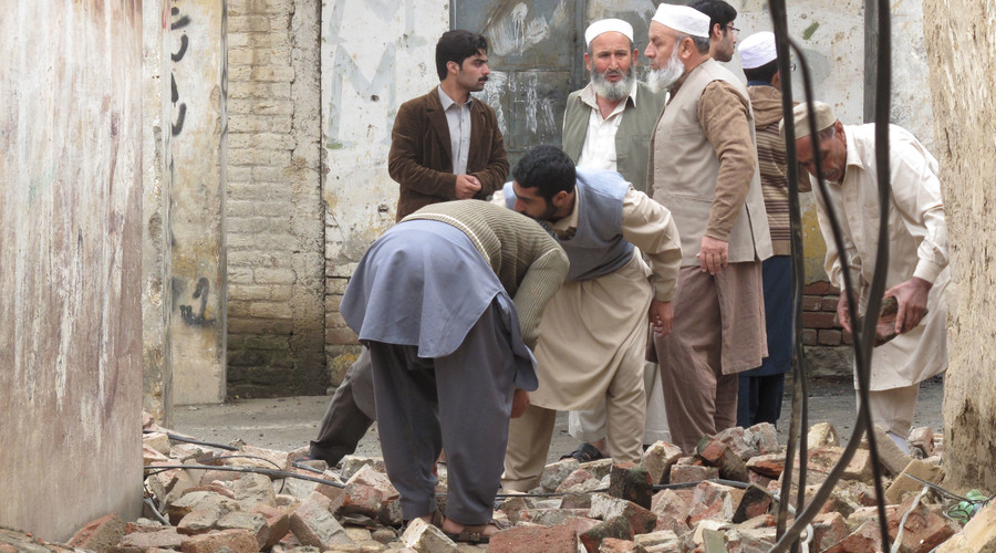 Residents gather to clear a path by removing rubble from a house after it was damaged by an earthquake in Mingora, Swat, Pakistan October 26, 2015. © Hazrat Ali Bacha