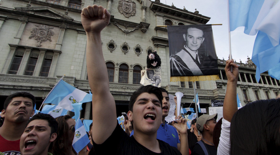 Demonstrators shout as they hold Guatemalan national flags and a picture of former Guatemalan President Jacobo Arbenz, during a protest against Guatemala's President Otto Perez in Guatemala City, Guatemala. © Josue Decavele