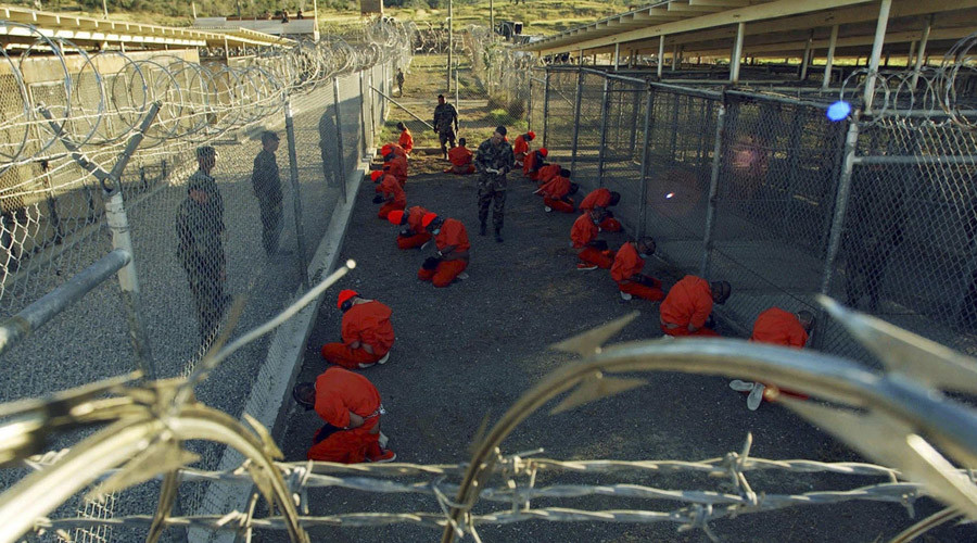 Detainees in orange jumpsuits sit in a holding area under the watchful eyes of military police during in-processing to the temporary detention facility at Camp X-Ray of Naval Base Guantanamo Bay © Stringer