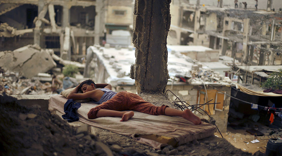 A Palestinian boy sleeps on a mattress inside the remains of his family's house, that witnesses said was destroyed by Israeli shelling during a 50-day war in 2014 summer, during a sandstorm in Gaza September 8, 2015. ©Suhaib Salem