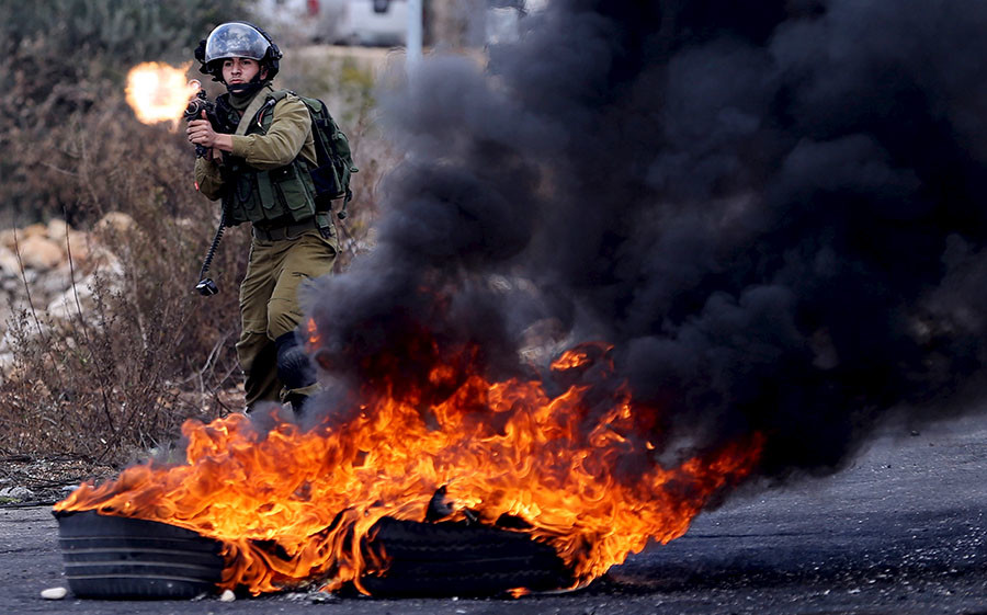 An Israeli soldier fires a weapon towards Palestinian protesters during clashes near the Jewish settlement of Bet El, near the West Bank city of Ramallah October 30, 2015. ©Mohamad Torokman