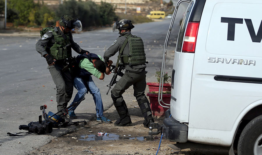 Israeli border policemen beat a Palestinian journalist during clashes with Palestinian protesters near the Jewish settlement of Bet El, near the West Bank city of Ramallah October 30, 2015. ©Mohamad Torokman