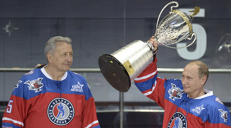 Russian President Vladimir Putin lifts a trophy as former hockey player Alexander Yakushev stands nearby after a gala game, opening a new season of the Night Ice Hockey League in Sochi, Russia, October 7, 2015 © Aleksey Nikolsky