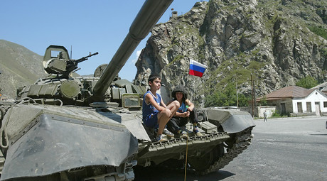 ARCHIVE PHOTO: Children sit on a Russian tank near the South Ossetian city of Tskhinvali on August 10, 2008 © Said Gutziev