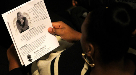 FILE PHOTO: A mourner reads the obituary from the program during the funeral service for Tamir Rice in Cleveland, Ohio December 3, 2014 © Aaron Josefczyk