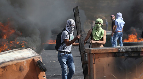 Masked Palestinian protesters take cover during clashes with the Israeli troops near the Jewish settlement of Bet El, near the West Bank city of Ramallah October 12, 2015. © Mohamad Torokman