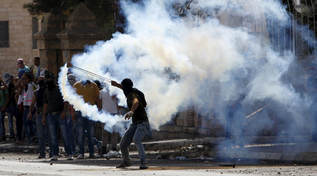 A Palestinian uses a sling to throw back a tear gas canister fired by Israeli troops during clashes in the West Bank city of Bethlehem October 14, 2015. © Mussa Qawasma