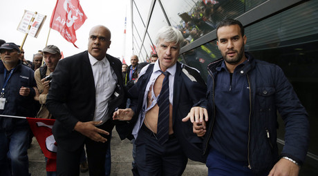 Director in charge of human resources of Air France long-haul flights, Pierre Plissonnier (C), nearly shirtless, runs away from the demonstrators, after several hundred employees stormed into the offices of Air France on October 5, 2015. © Kenzo Tribouillard
