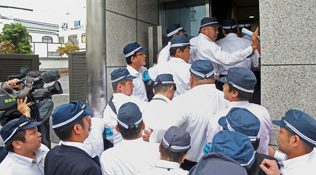 Police officers raid the headquarters of the