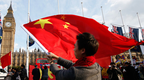 A supporter of China's President Xi Jinping waves a Chinese flag opposite Big Ben in Parliament Square ahead of Xi's address to both Houses of Parliament, in London, Britain, October 20, 2015. © Peter Nicholls