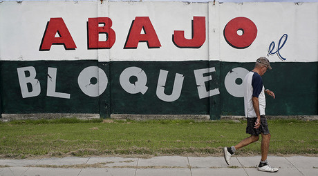 A man walks on a sidewalk in Havana October 27, 2015. The sign on the wall reads,