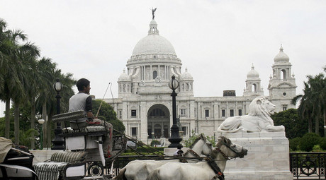 A horse-cart passes in front of the Queen Victoria Memorial in the eastern Indian city of Kolkata. © Jayanta Shaw