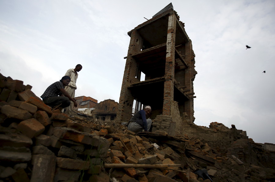 People clear debris from collapsed houses that were damaged during the earthquake in Bhaktapur July 14, 2015 © Navesh Chitrakar