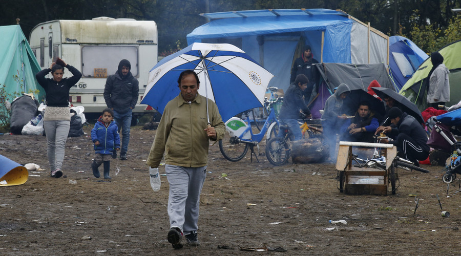 "Migrants are seen near their tents in the makeshift camp called the ""New Jungle"" as unseasonably cool temperatures arrive in Calais, northern France, October 21, 2015. © Pascal Rossignol"
