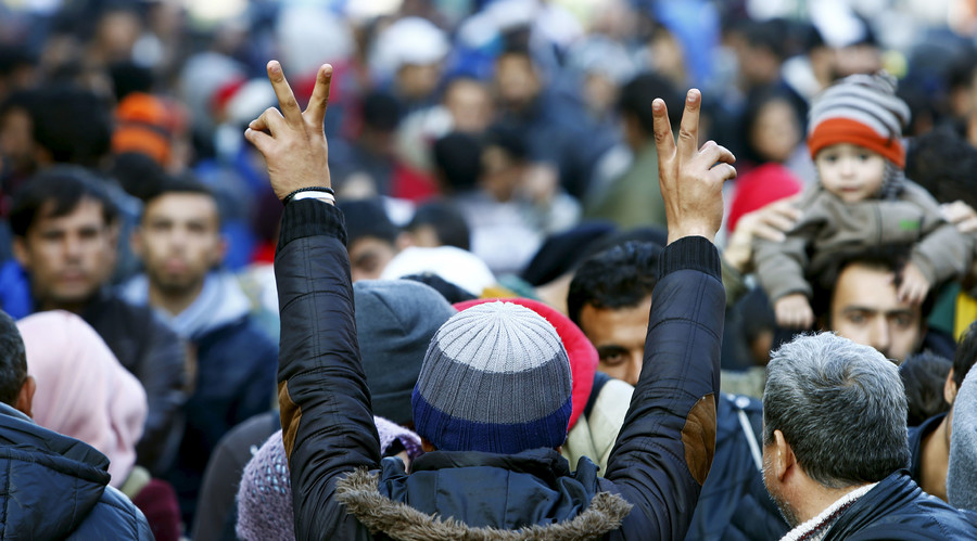 Migrants gesture after arriving at the Austrian-German border in Achleiten near Passau, Germany, October 27, 2015. Michaela Rehle