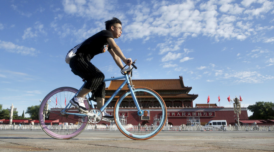 A man cycles past Beijing's Tiananmen Gate on a sunny day in the morning, August 22, 2015. © Jason Lee