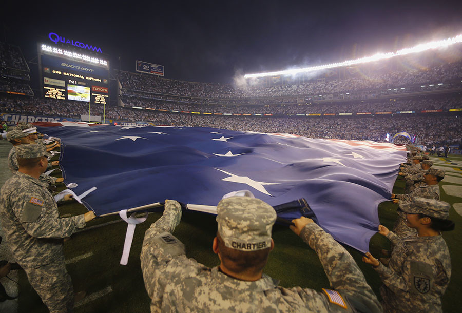 © California National Guard members hold out a giant American flag before the start of the Monday Night NFL football game between the Houston Texans and the San Diego Chargers in San Diego, California September 9, 2013. © Mike Blake