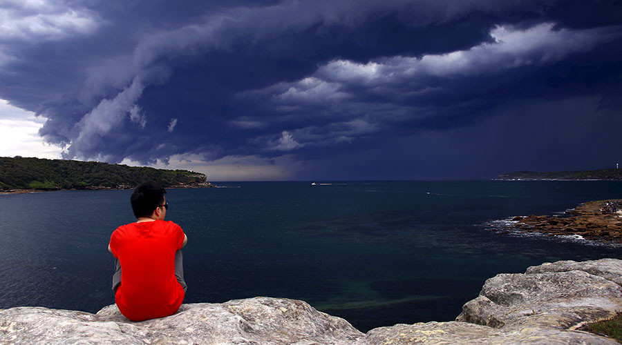 A Chinese tourist watches storm clouds moving along the coast towards the city of Sydney, Australia, November 6, 2015. © David Gray