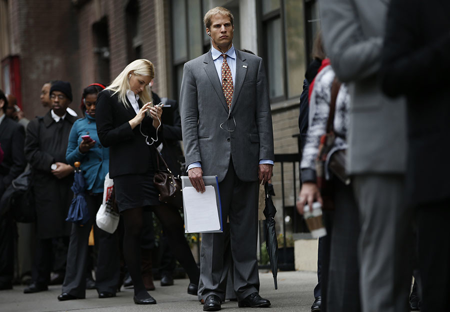 Job seekers stand in line to meet with prospective employers at a career fair in New York City. ©Mike Segar