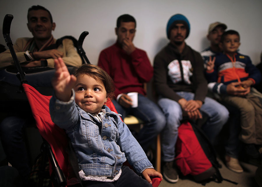 A young girl reacts moments after refugees from Syria and Iraq arrived at a refugee centre in Champagne-sur-Seine, near Paris, France, September 9, 2015. © Christian Hartmann