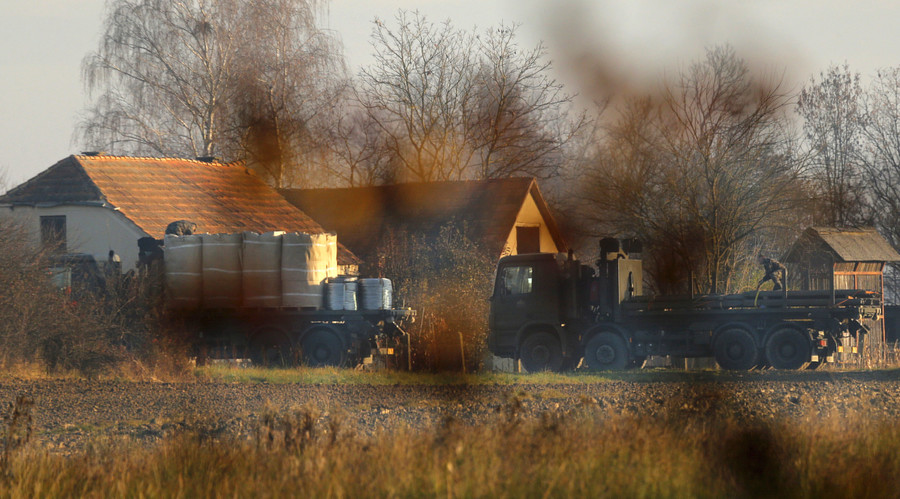 Army trucks and soldiers are seen in the village Veliki Obrez, Slovenia, November 11, 2015. © Antonio Bronic