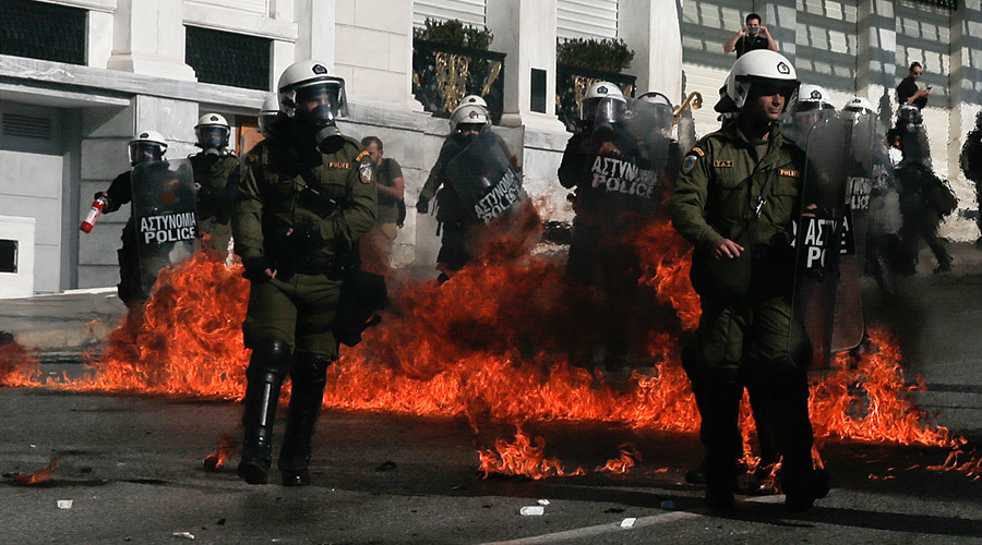 Riot policemen walk by fires caused by petrol bombs thrown by youths following brief clashes between police and protesters during a 24-hour general strike in central Athens, Greece November 12, 2015. © Alkis Konstantinidis