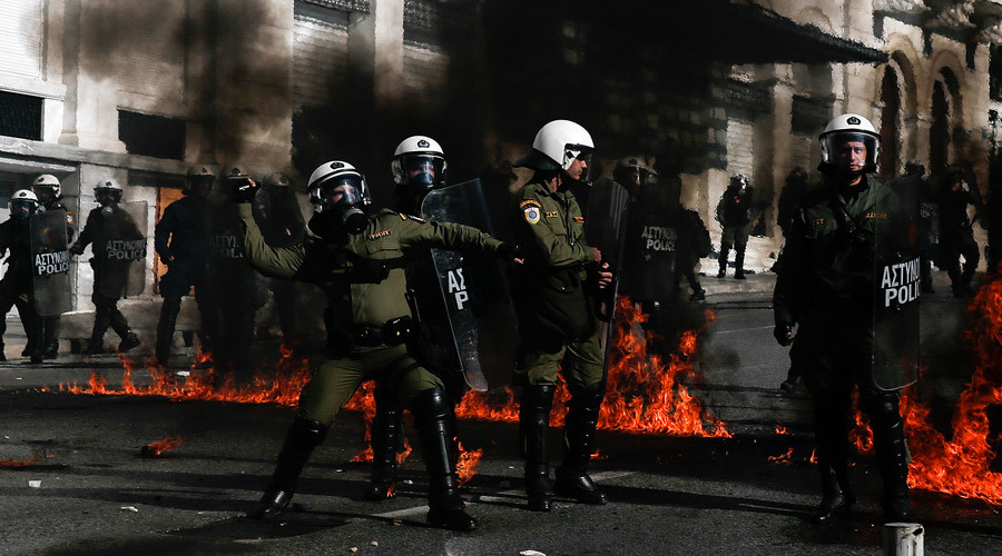 A riot policeman (L) prepares to throw a teas gas canister as others walk by fires caused by petrol bombs thrown by youths following brief clashes between police and protesters during a 24-hour general strike in central Athens, Greece, November 12, 2015 © Alkis Konstantinidis