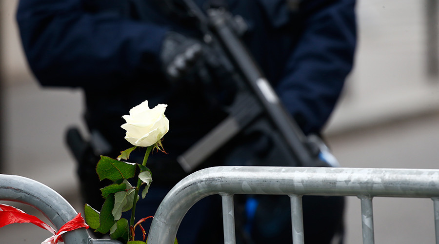 A white rose is attached to a barrier as a French policeman with an automatic weapon secures the area near the Bataclan concert hall the day after a series of deadly attacks in Paris, France, November 14, 2015 © Benoit Tessier