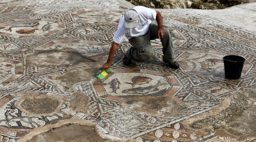 An Israeli antiquity authority worker cleans a mosaic which was part of a courtyard of a villa dated some 1,700 years ago, in Lod, south to Tel Aviv, November 16, 2015. © Nir Elias