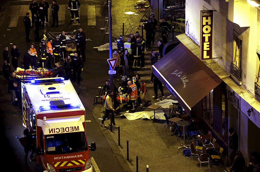 General view of the scene with rescue service personnel working near covered bodies outside the Le Carillon restaurant following shooting incidents in Paris, France, November 13, 2015. © Philippe Wojazer