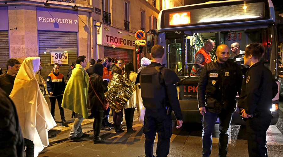 French police stand near people warming up on a street before being evacuated by bus near the Bataclan concert hall following fatal attacks in Paris, France, November 14, 2015 © Philippe Wojazer
