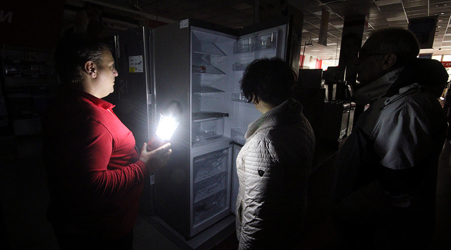 An employee (L) speaks with people at an electronics store, with the power turned off inside, in Simferopol, Crimea, November 22, 2015 © Pavel Rebrov