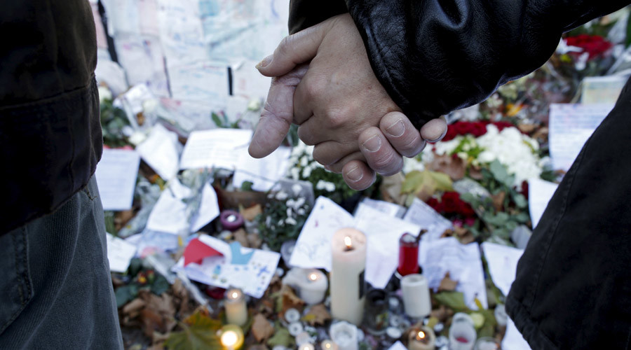 People stand hand in hand in front of candles and messages displayed in front of the Bataclan concert hall after last week's deadly attacks in Paris, France, November 22, 2015. © Christian Hartmann