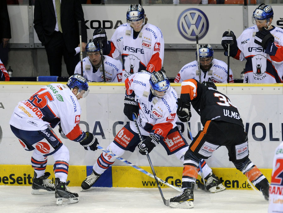 Jason Ulmer (R) of Grizzly Wolfsburg fights for the puck with Travis James Mulock (L) and Stefan Ustorf of Eisbaeren Berlin during the third match of the final best-of-five series of the German Ice Hockey League in Wolfsburg, April 19, 2011. ©Fabian Bimmer
