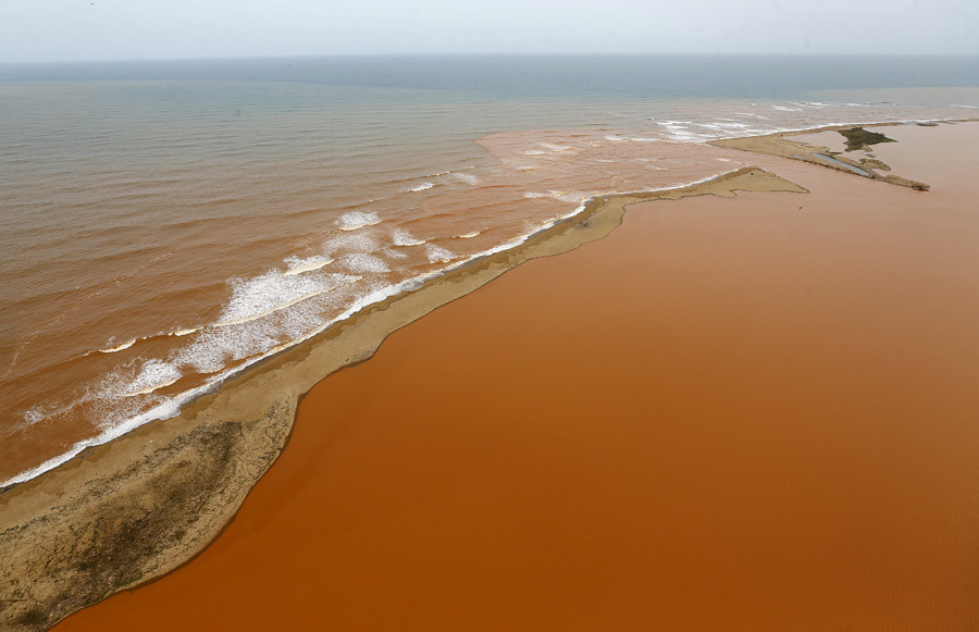 An aerial view of the Rio Doce (Doce River), (bottom) which was flooded with mud after a dam owned by Vale SA and BHP Billiton Ltd burst, at an area where the river joins the sea (top) on the coast of Espirito Santo in Regencia Village, Brazil, November 23, 2015. © Ricardo Moraes