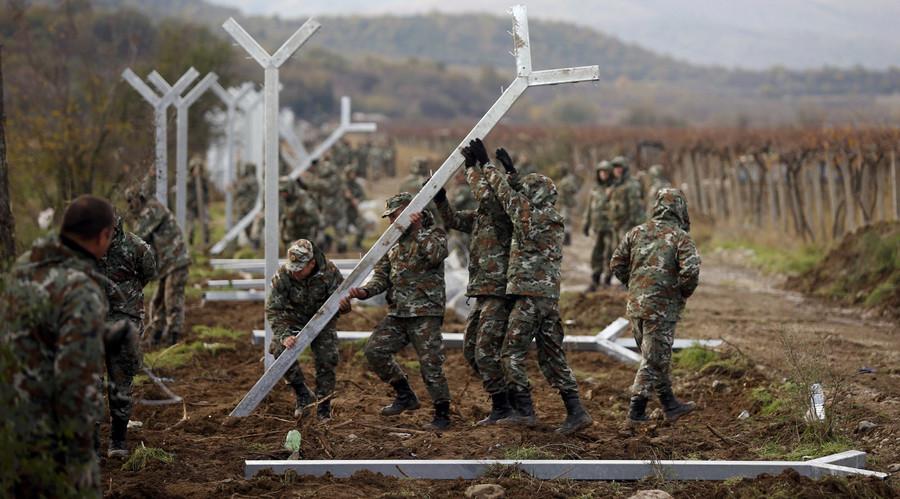 Macedonian soldiers erect a metal fence on the border with Greece, near Gevgelija, Macedonia, November 28, 2015. © Stoyan Nenov