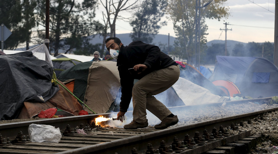 A stranded migrant throws a tear gas canister back to Macedonian police officers, as minor clashes broke out during a protest against the building of a metal fence at the Greek-Macedonian borders near the village of Idomeni, Greece November 28, 2015. © Yannis Behrakis