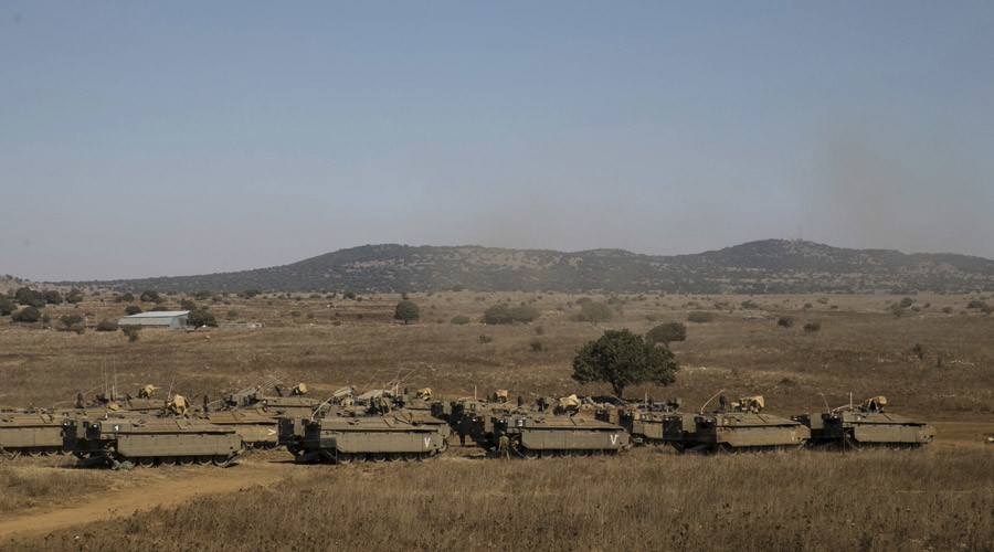 Israeli soldiers walk next to armoured personnel carriers (APC) in the Israeli-occupied Golan Heights, near the ceasefire line between Israel and Syria © Baz Ratner