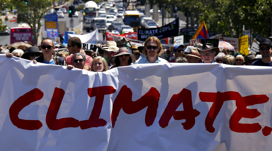 People hold placards and banners as they participate in a march ahead of the Paris World Climate Change Conference, along the main street of Adelaide, South Australia, November 29, 2015. © David Gray