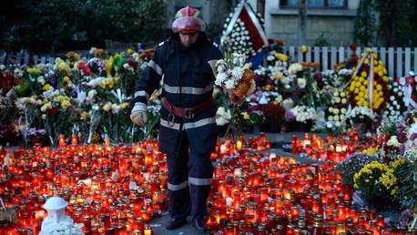 A fireman walks between lit candles with flowers as thousands mourn the victims of a nightclub fire in Bucharest, Romania.