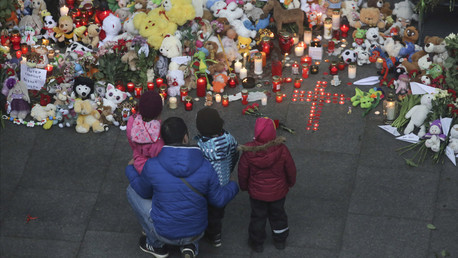 A man and children mourn near a makeshift memorial outside Pulkovo airport in St. Petersburg, Russia November 1, 2015. © Peter Kovalev