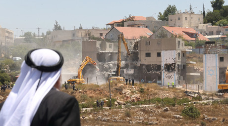A Palestinian man watches Israeli heavy machinery as they demolish vacant apartment blocs by order of Israel's high court, in the West Bank Jewish settlement of Beit El near Ramallah July 29, 2015. © Mohamad Torokman
