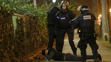 A man lies on the ground as French police check his identity near the Bataclan concert hall following fatal shootings in Paris, France, November 13, 2015. © Christian Hartmann