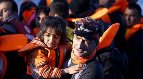 A volunteer carries a Syrian refugee girl off an overcrowded raft after landing at a rocky beach in the Greek island of Lesbos, November 19, 2015. © Yannis Behrakis