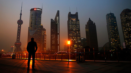 A man looks at the Pudong financial district of Shanghai © Carlos Barria