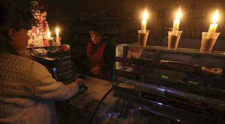 A customer visits a grocery lit with candles due to a power cut, in Simferopol, Crimea, November 22, 2015. © Pavel Rebrov