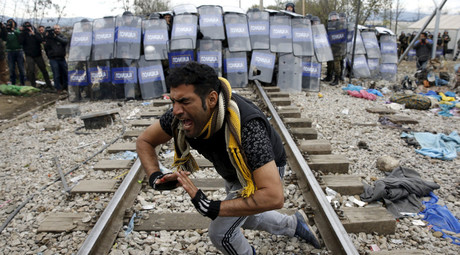 A stranded migrant reacts in front of a Macedonian police cordon as they clash after a migrant was injured when he climbed on top of a train wagon, near the village of Idomeni, Greece, November 28, 2015. © Yannis Behrakis