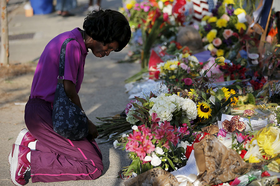 Patricia Bailey prays at a makeshift memorial outside the Emanuel African Methodist Episcopal Church in Charleston, South Carolina June 20, 2015, three days after a mass shooting which left nine people dead during a bible study at the church. © Brian Snyder